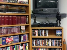 Library media corner containing DVDs, CDs, and VHS tapes.
